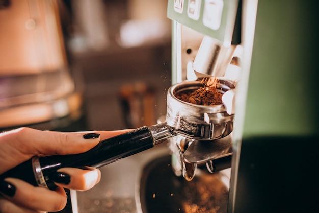 コーヒーマシンでコーヒーを準備するバリスタ