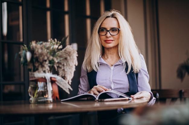 カフェの外に座って雑誌を読んで高齢者の実業家