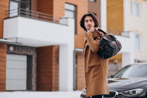 彼の車に家から歩いて若いハンサムな実業家