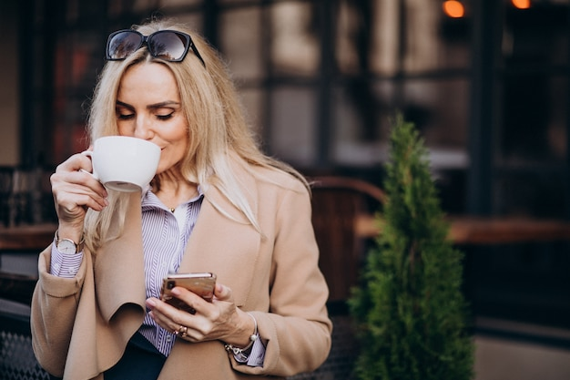 Пожилая деловая женщина пьет кофе возле кафе и разговаривает по телефону