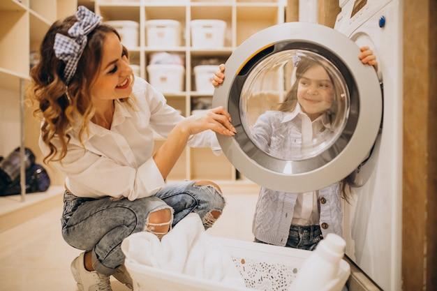 Мать с дочерью стирает в прачечной самообслуживания