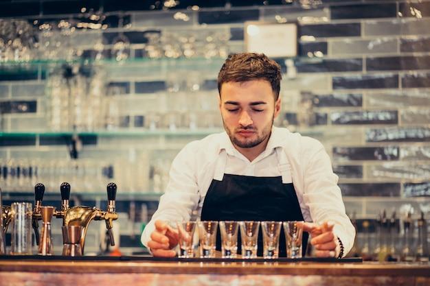 Красивый бармен человек делает пить и коктейли за прилавком