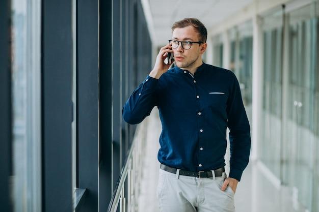 Молодой красивый мужчина разговаривает по телефону в офисе