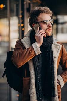 空港で電話で話している若いハンサムな男
