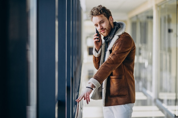 Молодой красивый мужчина в аэропорту разговаривает по телефону