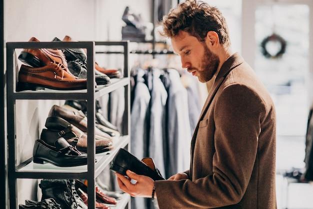 Молодой красавец, выбирая обувь в магазине