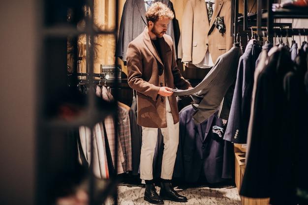 Молодой красавец, выбирая одежду в магазине