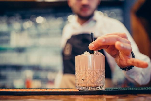 Красивый бармен делает пить и коктейли на прилавке