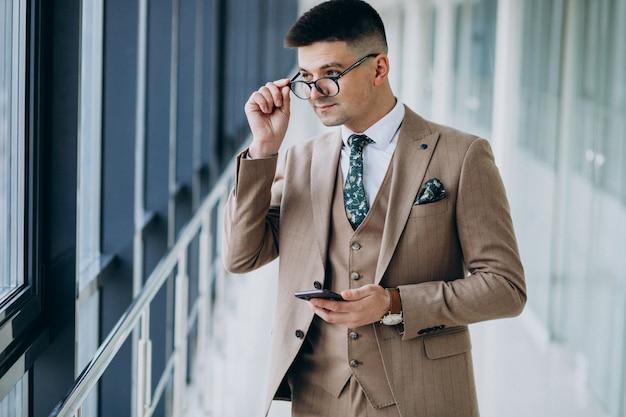 オフィスで電話で立っている若いハンサムなビジネス人