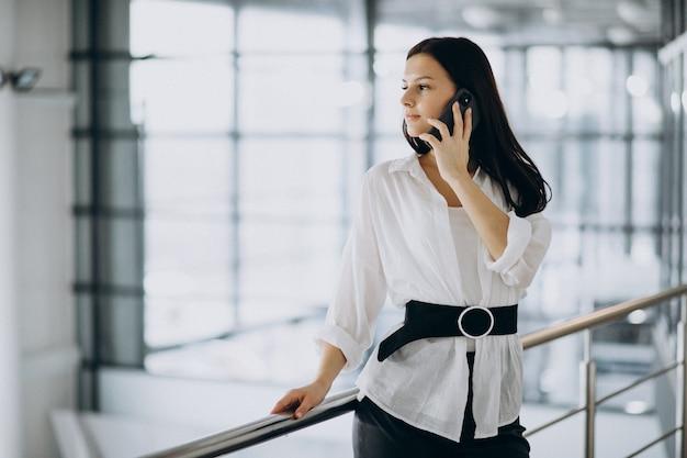 オフィスで電話を使用して若いビジネス女性