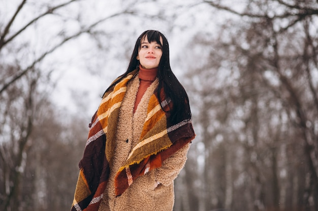 Молодая счастливая женщина в теплой одежде в зимнем парке