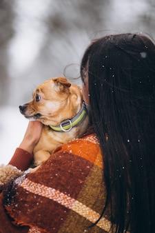 Молодая женщина вне парка с ее маленькой собакой зимой