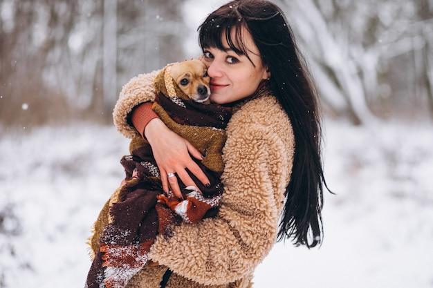 冬に彼女の小さな犬と公園の外の若い女性