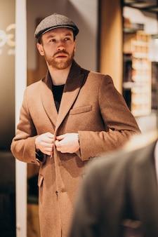 お店で帽子を選択する若いハンサムな男