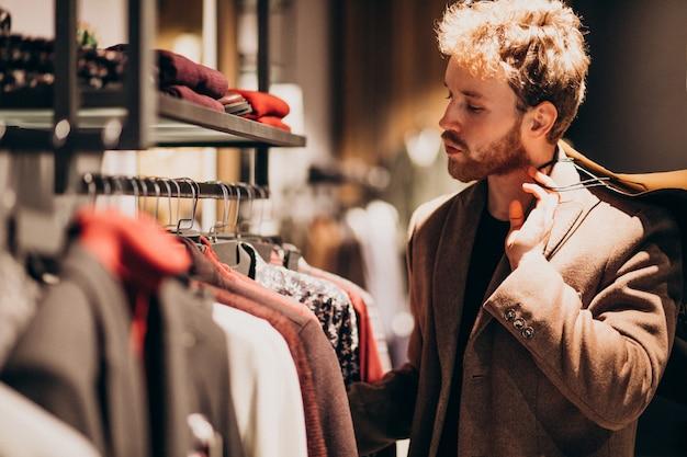 Молодой красавец, выбирая ткань в магазине