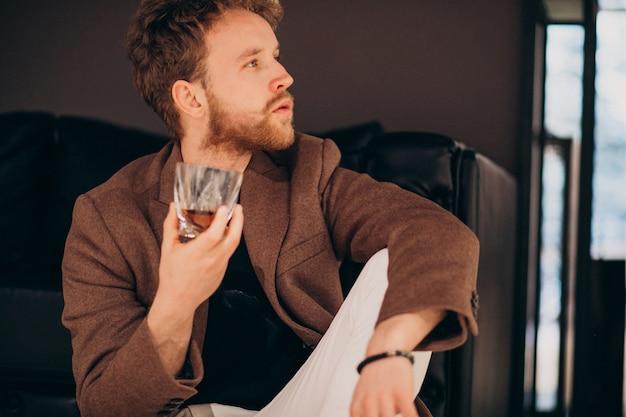 Красивый бородатый мужчина пьет виски