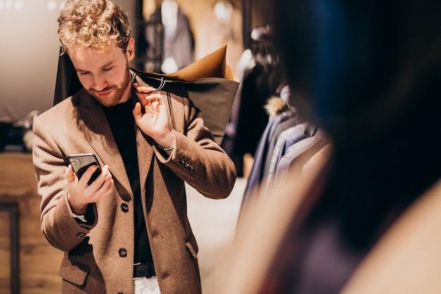 電話で話している紳士服店で若い男