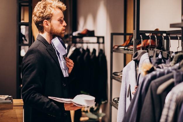 お店でシャツを選択する若いハンサムな男