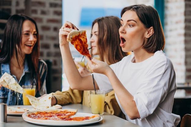 Три подружки с пиццей в баре