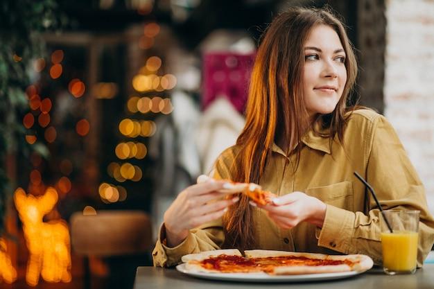 バーでピザを食べる若いきれいな女性