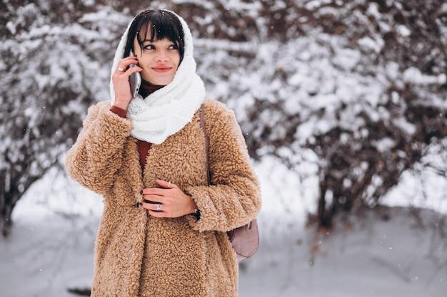 冬の公園で暖かい布で若い幸せな女