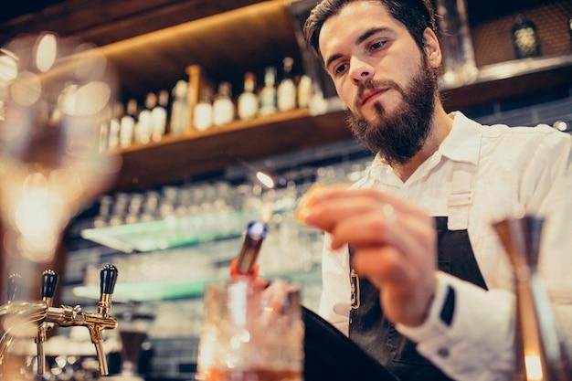 カウンターで飲むとカクテルを作るハンサムなバーテンダー