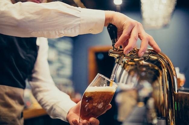 Мужской бармен наливает пиво в пабе