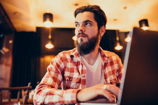 Молодой бородатый человек работает на ноутбуке в баре