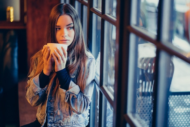 Молодая красивая женщина пьет кофе в баре
