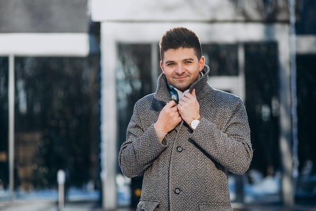 Пальто молодого красивого человека нося снаружи в парке