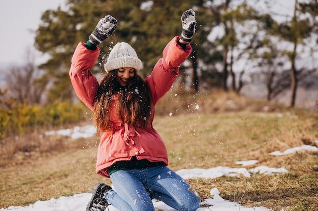 Молодая женщина в зимнем парке счастливым