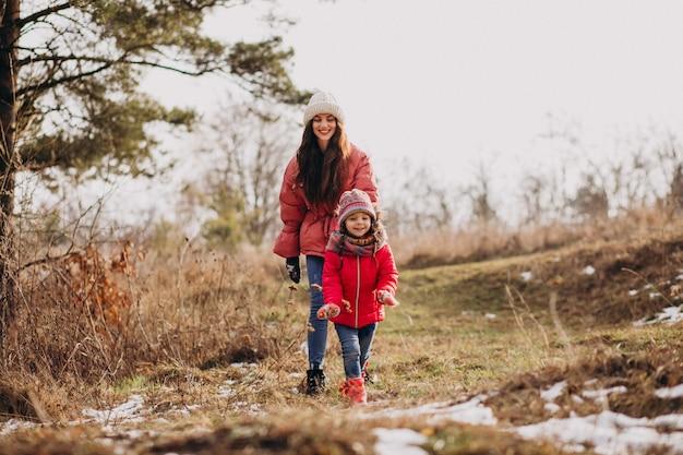Мать с маленькой дочерью в зимнем лесу