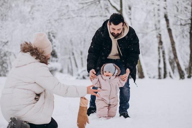 雪だらけの冬の森の小さな娘と若い家族