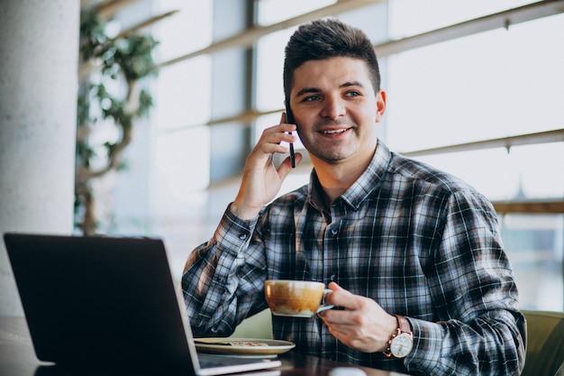 カフェでラップトップを使用して若いハンサムな実業家