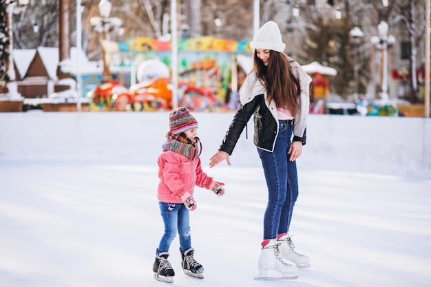 Мать с дочерью учат катанию на коньках на катке