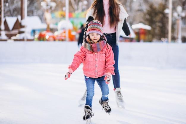 スケートリンクでアイススケートを教える娘と母