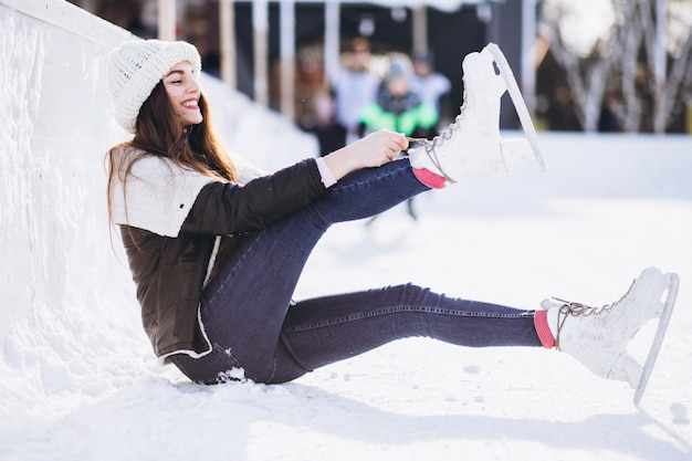 Молодая женщина на коньках на катке в центре города