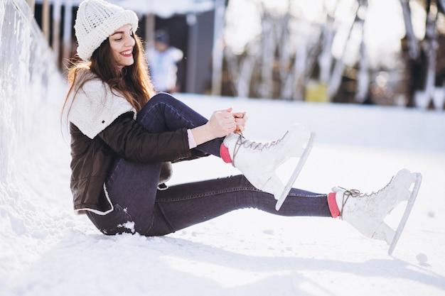 市内中心部のスケートリンクでスケートの若い女性