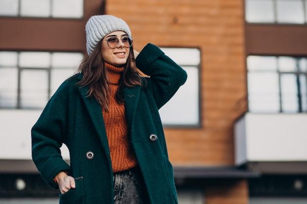 家で暖かいコートの若いきれいな女性