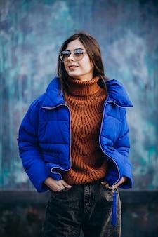 青い冬のジャケットの若い魅力的な女性