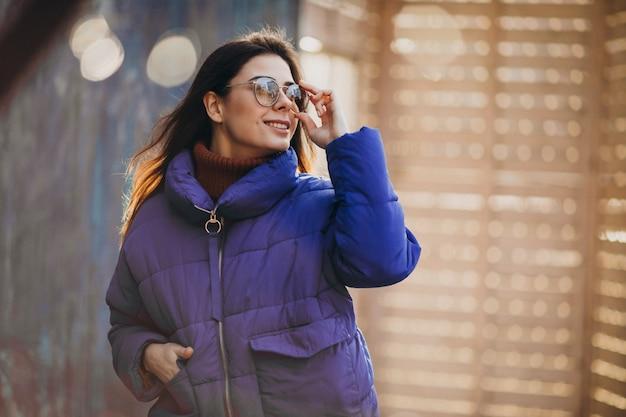 Молодая привлекательная женщина в синей зимней куртке