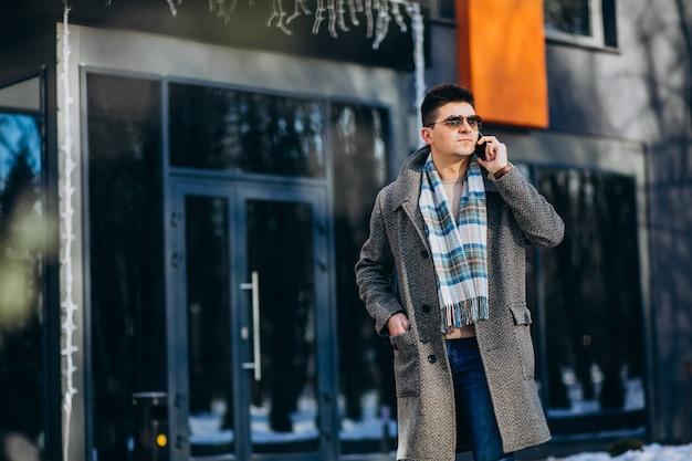 Молодой красивый мужчина на улице с помощью телефона