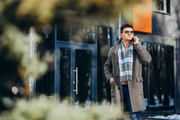電話を使用して外の若いハンサムな男