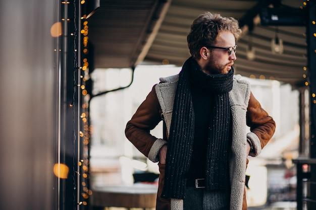 通りを歩いて冬服で若いハンサムな男