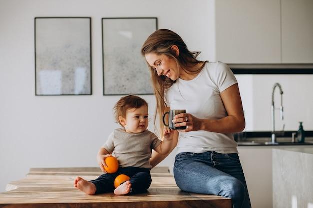 自宅で水を飲む幼い息子を持つ若い母親