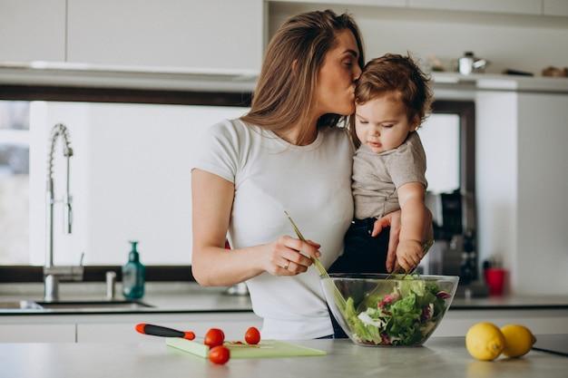 Молодая мать с сыном делает салат на кухне