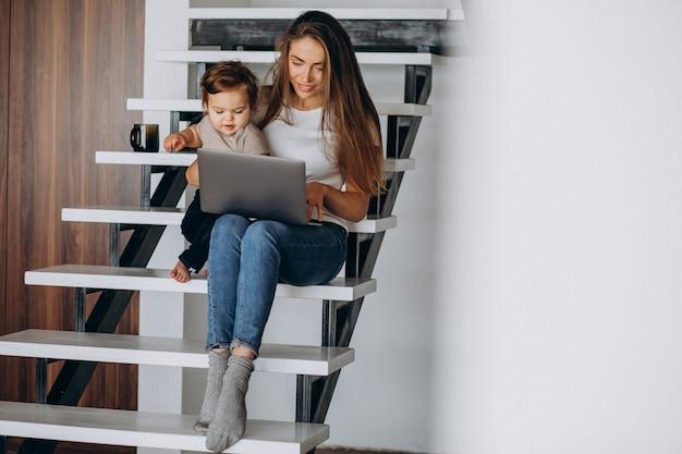 Молодая мать работает из дома на ноутбуке с маленьким сыном