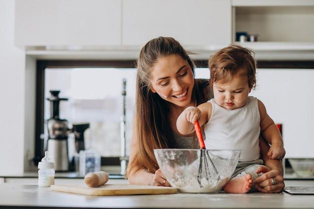 キッチンで料理をして彼女の幼い息子を持つ若い母親