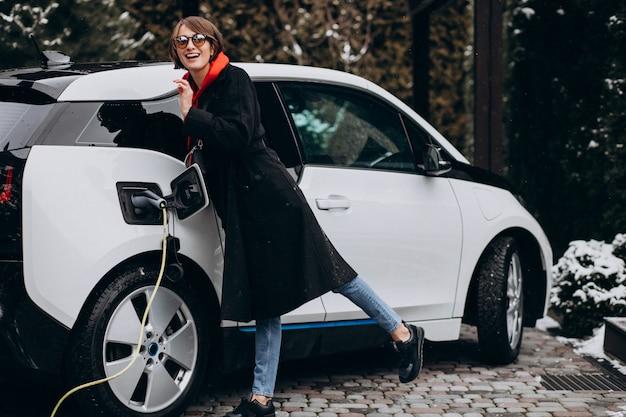 Женщина заряжает электро автомобиль возле своего дома