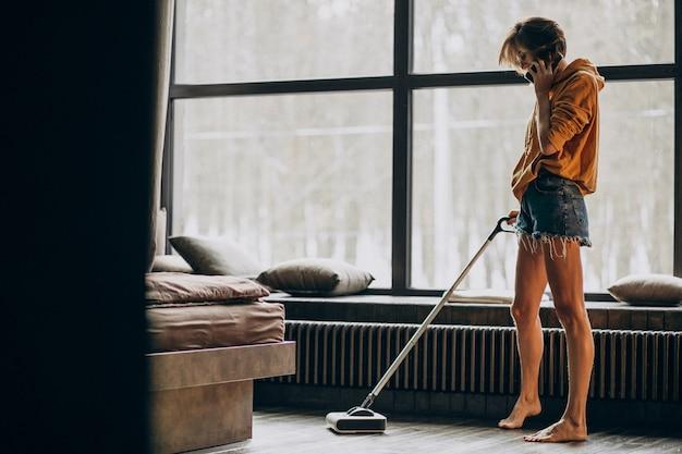 自宅で掃除機をかけ、踊る女性